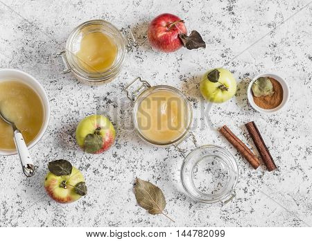 Homemade apple sauce in glass jars on light background. Top view