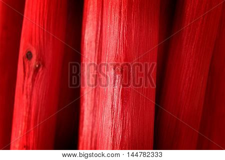 Natural wooden painted red pole. Abstract textured background.