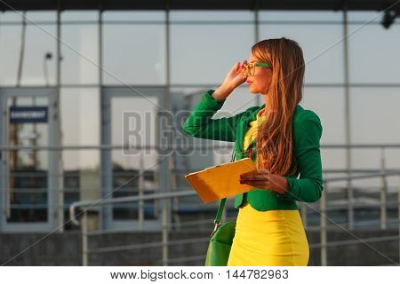 Business woman controls the works. Young attractive girl in a jacket corrects glasses and holding a checklist.