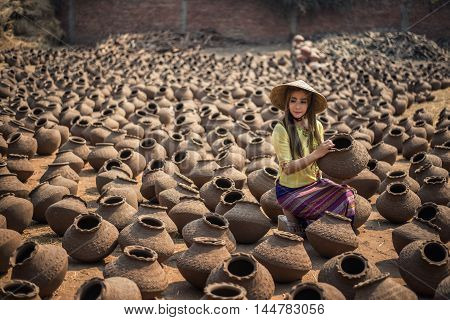 Beautiful Worker Women Happy asian traditional harvest at Mandalay Myanmar carrying pots in Myanmar traditional costume identity culture of Myanmar