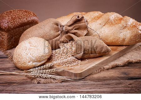 Fresh bread, sweet pastries, baked goods, harvest on the farm, great food, ears of wheat, burlap sack of grain, healthy food, a table of old wood, close-up bread, spilling wheat