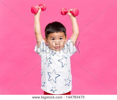 Little kid weighting up dumbbell