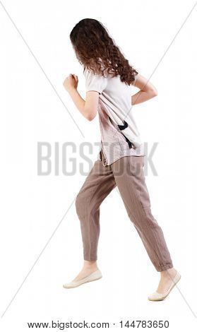 side view of running woman. beautiful girl in motion. Long-haired curly girl runs past the camera.