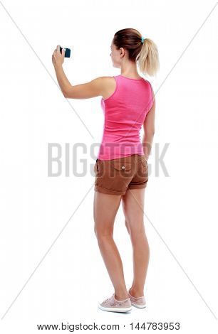 back view of standing young beautiful woman and using a mobile phone. Isolated over white background. Sport blond in brown shorts photographed on a compact camera.