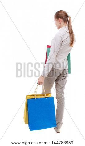 back view of woman with shopping bags. Isolated over white background. Skinny girl in white denim suit standing with paper bags.
