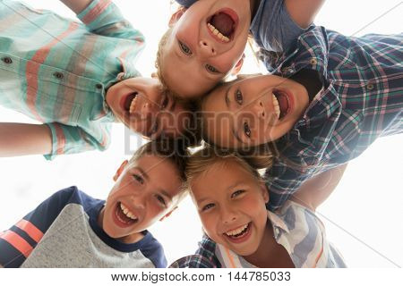 childhood, leisure, friendship and people concept - group of smiling happy laughing children faces in circle