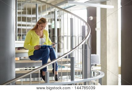 education, high school, university, learning and people concept - smiling student girl reading book sitting on stairs