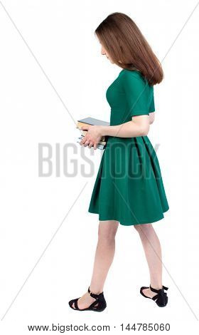 Girl carries a heavy pile of books. back view. slender brunette in a green short dress stands sideways and holds a stack of books.