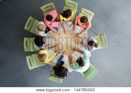 education, school, teamwork, gesture and people concept - group of international students with books sitting and pointing finger to center of table from top