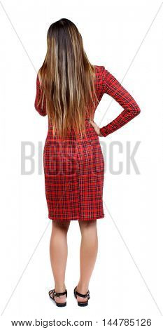 back view of standing young beautiful woman. girl watching. girl in red plaid dress with hands on the side and talking on the phone.