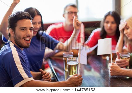 people, leisure, rivalry and sport concept - friends or football fans with white flags drinking beer and watching soccer game or match at bar or pub