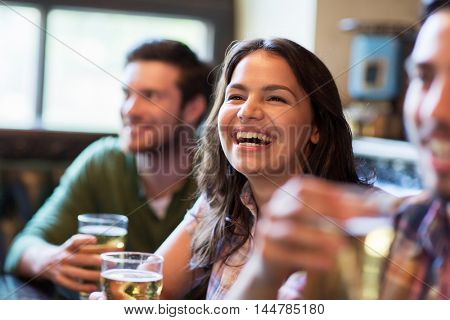 people, leisure, friendship, emotion and communication concept - happy woman with her friends drinking beer at bar or pub and laughing