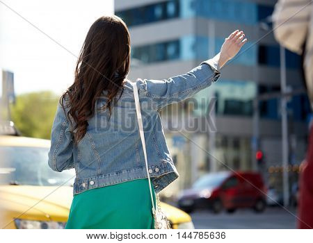gesture, transportation, travel, tourism and people concept - young woman or teenage girl catching taxi on city street or hitch-hiking