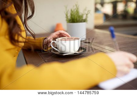 leisure and people concept - close up of young woman or teenage girl with cup drinking cocoa and writing to notebook at city street cafe terrace