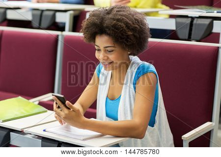 education, high school, university, learning and people concept - african student girl with smartphone on lecture