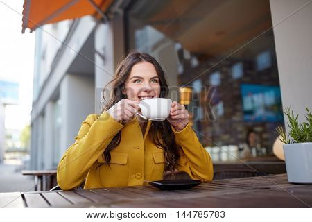 drinks and people concept - happy young woman or teenage girl with cup drinking cocoa at city street cafe terrace
