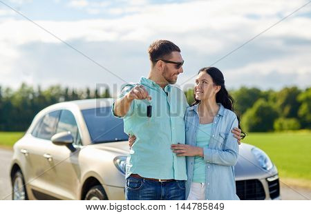 transport, road trip, travel, family and people concept - happy man and woman with car key hugging