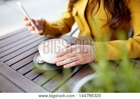 communication, technology, leisure and people concept - close up of young woman or teenage girl texting on smartphone and drinking cocoa at city street cafe terrace