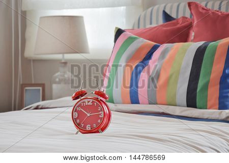 Red Clock On White Blanket And Colorful Striped Pillows