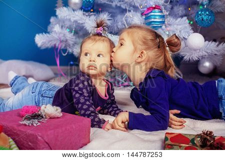 two little sisters lying near the tree. The concept of New Year and Christmas