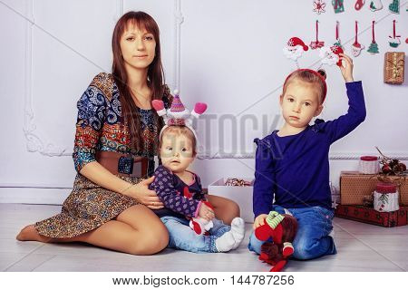 mother of two young daughters in the room. The concept of New Year and Christmas