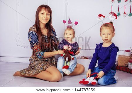 mother and two daughters in the room. The concept of New Year and Christmas