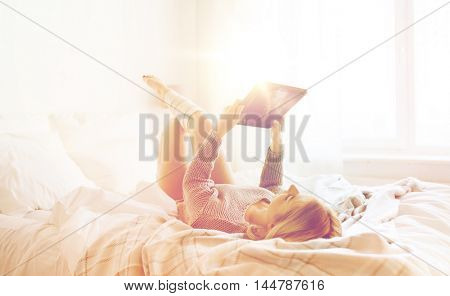 technology, internet and people concept - happy young woman lying in bed with tablet pc computer at home bedroom