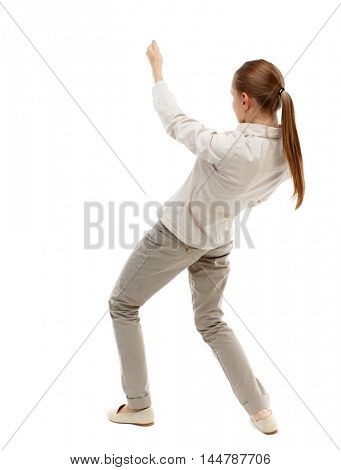 back view of standing girl pulling a rope from the top or cling to something. Isolated over white background. Skinny girl in white denim suit pulls the top rope.