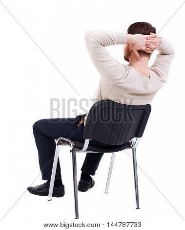 back view of business man sitting on chair. bearded man in a white warm sweater sits on a chair with his hands behind his head. Side view.