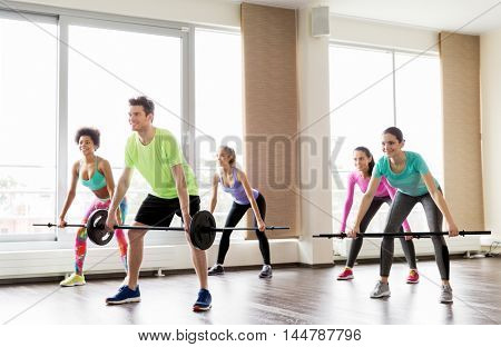 fitness, sport, training and lifestyle concept - group of people exercising with barbell bars in gym