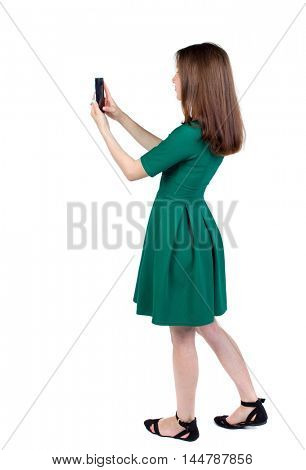 back view of standing young beautiful woman using a mobile phone. girl watching. slender brunette in a green short dress stands sideways and photographed on a smartphone.