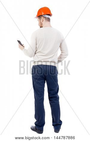 Backview of business man in construction helmet stands and enjoys tablet or using a mobile phone. bearded man in a white warm sweater and an orange helmet looks into the phone.