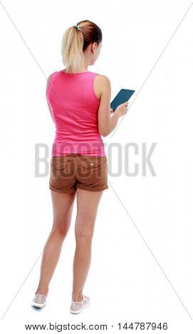 back view of standing young beautiful woman using a mobile phone or tablet computer. Isolated over white background. Sport blond in brown shorts reading an e-book.