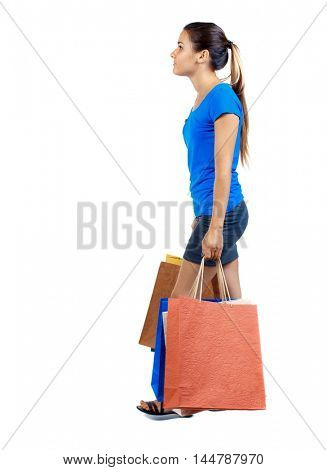 side view of going woman with shopping bags . beautiful girl in motion girl in a short skirt and a blue T-shirt bears the heavy bags.
