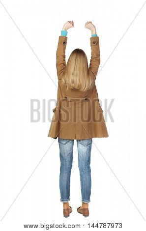Back view of woman. Raised his fist up in victory sign. blonde in a brown cloak raised his fists up.