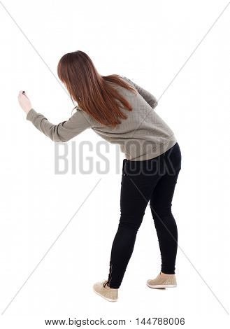 back view of writing beautiful woman. Isolated over white background. A young girl in a gray jacket leaned marker drawing.