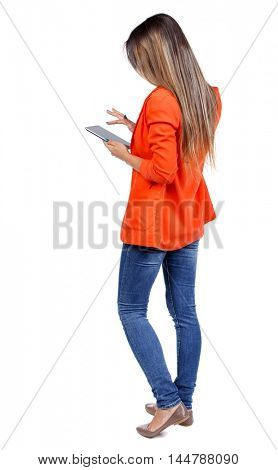 back view of standing young beautiful woman using a mobile phone or tablet computer. girl watching. girl in a red jacket stands sideways and running in the plate.