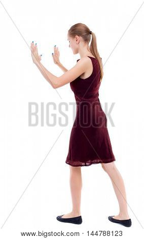 back view of woman pushes wall. Isolated over white background. girl in a burgundy dress pushing in the side load.
