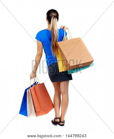 back view of woman with shopping bags. backside view of person. girl in a short skirt and a blue T-shirt slung over his shoulder shopping bags.