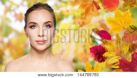 beauty, people, season and health concept - beautiful young woman face over autumn leaves background
