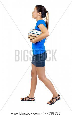 Girl comes with stack of books. side view. girl in a short skirt and a blue T-shirt goes to the side with books and looking up.