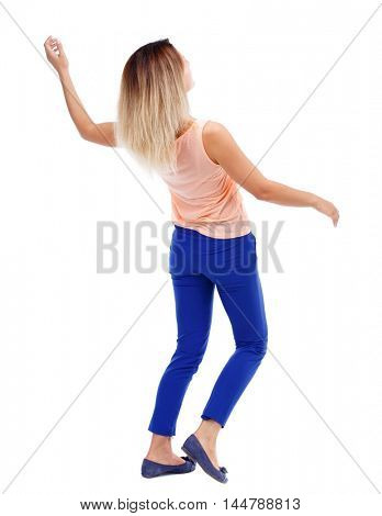 Balancing young woman. or dodge falling woman. Rear view people collection. blonde in a pink t-shirt dodges.