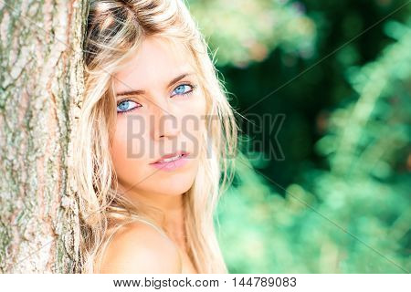 Portrait Of Beautiful Blond Girl With Blue Eyes In Nature