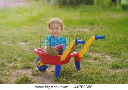 Little boy toddler playing with colorful children's plastic building wheelbarrow in the yard in the summer