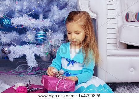 little girl in a dress near the tree unpacks gifts. The concept of New Year and Christmas