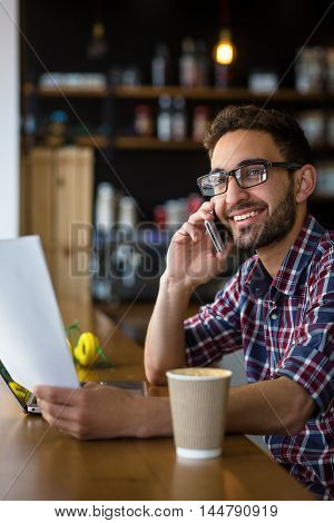 Portrait of cheerful handsome freelance man in glasses speaking over mobile or smart phone, looking at camera and reading something from document in restaurant or cafe.