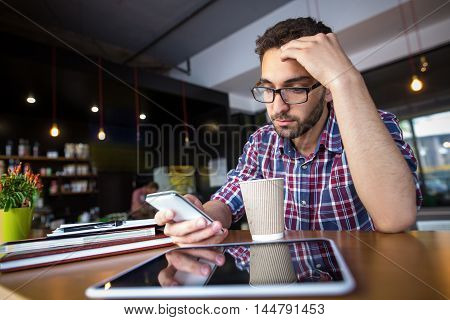 Portrait if serious breelnace or business man or student using mobileor smart phone. Handsome man in glasses typing messages.