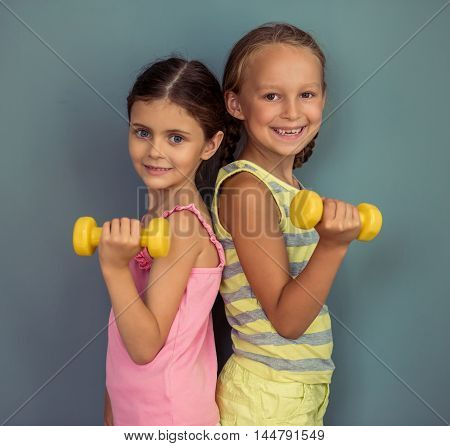 Two cute little girls are holding dumbbells looking at camera and smiling standing on gray background
