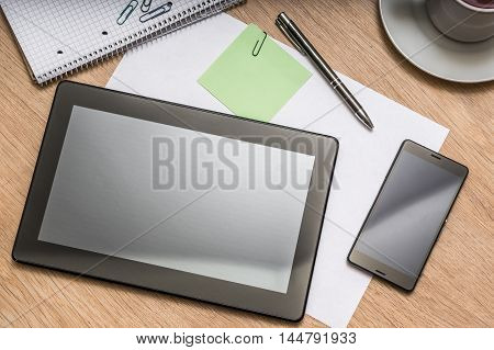 Tablet, Mobile Phone, Pen, Note And Cup Of Coffee On Table