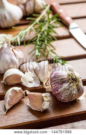Garlic and rosemary on wooden table.
